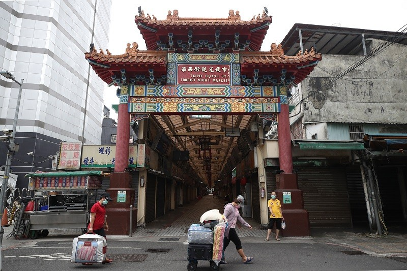 萬華區華西街夜市大多數店家受到疫情影響,都拉下鐵門暫停營業。中央社