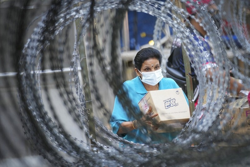 A resident wearing a face mask collects her package behind barbed wire in Kuala Lumpur, Malaysia, Friday, May 28, 2021.