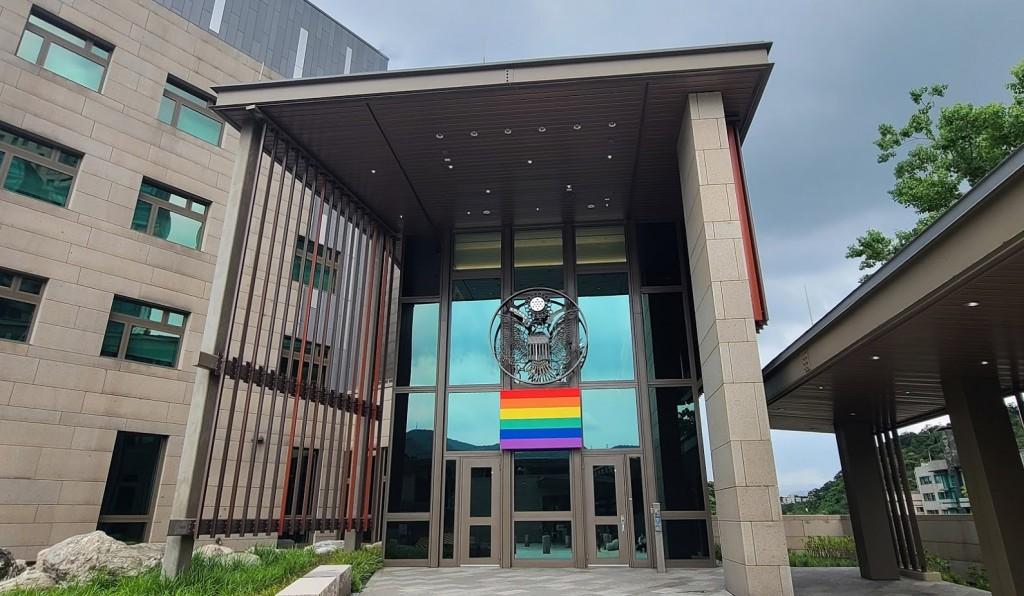 美國在台協會今(1)日於臉書上秀出大樓門口高掛彩虹旗的照片,並祝大家2021驕傲月快樂!(圖/AIT)