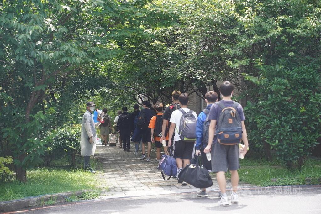 中國文化大學校內大倫館有4名學生確診武漢肺炎,校方已安排住宿生依序排隊前往快篩場所。(圖/中央社)