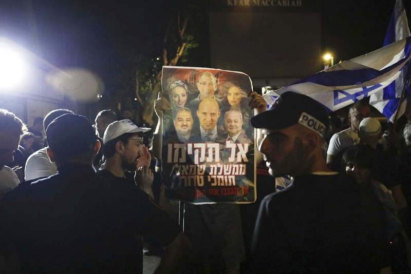 Israeli police officers stand guard as right wing protesters chant slogans in the central Israeli city of Ramat Gan,June 2, 2021.