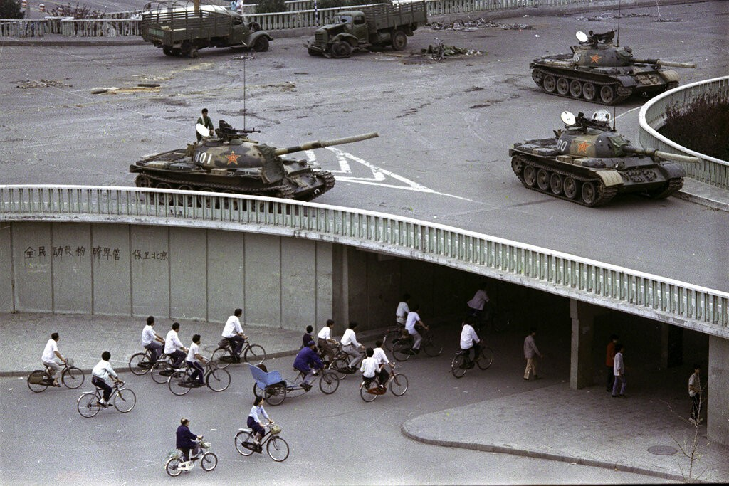 In this June 6, 1989, file photo, bicycling commuters pass through a tunnel as above on the overpass military tanks are positioned in Beijing, two day...