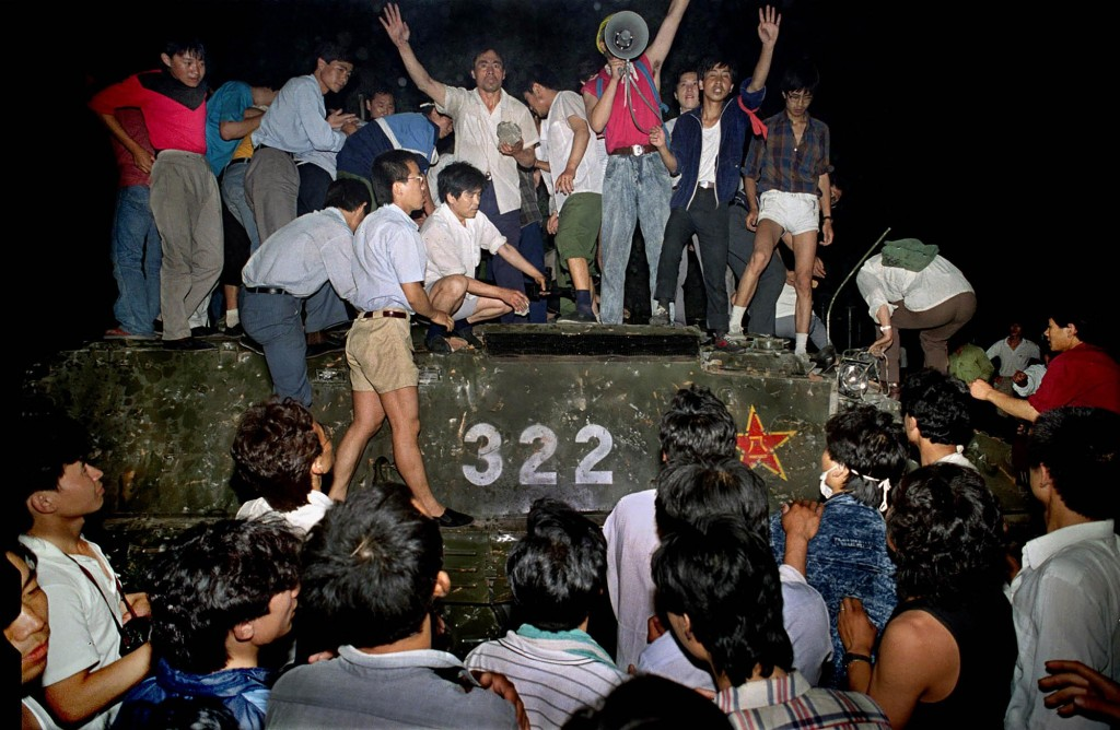 In this early June 4, 1989, file photo, civilians hold rocks as they stand on a government armored vehicle near Chang'an Boulevard in Beijing.&nbs...