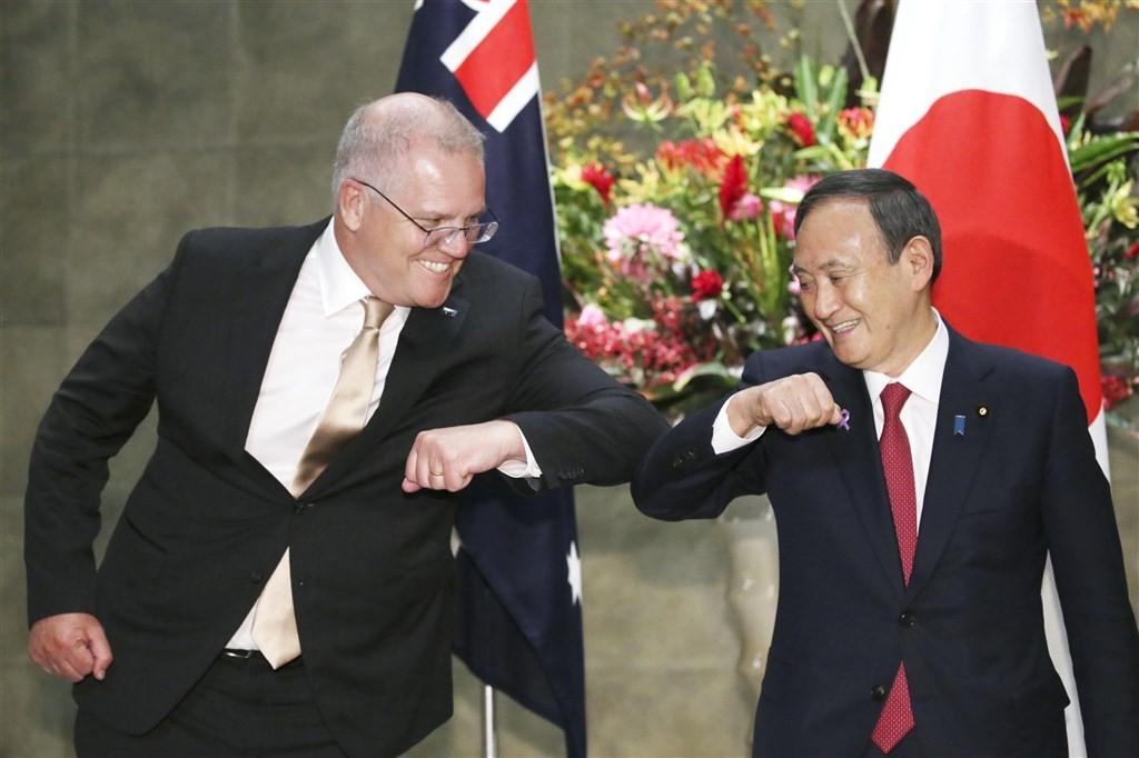 澳洲總理莫里森(左)去年與日本與首相菅義偉(右)會談,推動日本自衛隊與澳洲軍方簽署聯合訓練等協定。(圖/中央社)