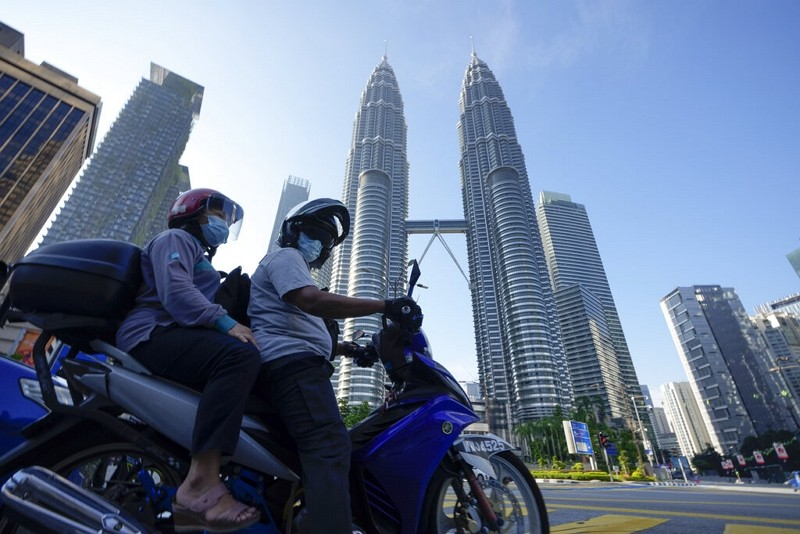 Motorists wearing face masks wait in front of the Twin Towers during the first day of Full Movement Control Order (MCO) in Kuala Lumpur, Malaysia, Tue...