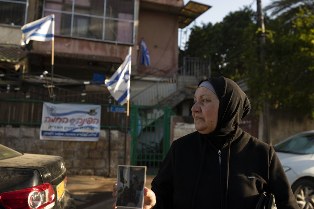 Maryam Ghawi, a Palestinian, holds a family photo taken in the home behind her that is now occupied by Israeli settlers in the Sheikh Jarrah neighborh...