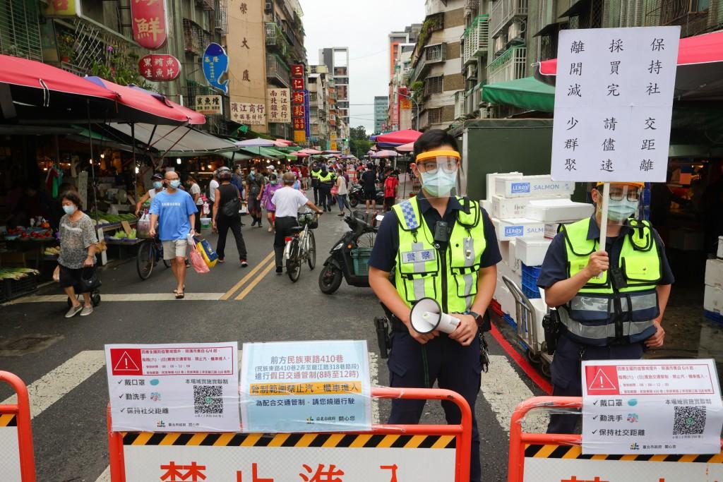 國內COVID-19疫情嚴峻,政府呼籲民眾減少採買次數避免群聚,台北市警方6日在傳統市場入口處管制並進行相關宣導。