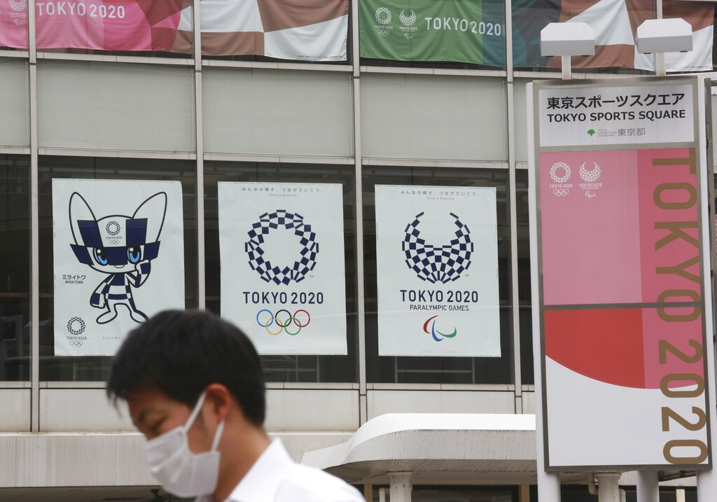 A man wearing a face mask to protect against the spread of the coronavirus walks by posters to promote the Tokyo Olympic Games in Tokyo Monday, June 7...