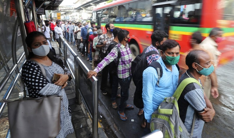 People wearing face masks as a precaution against the coronavirus stand in a queue as they wait at a bus stop in Mumbai, India, June 7, 2021.