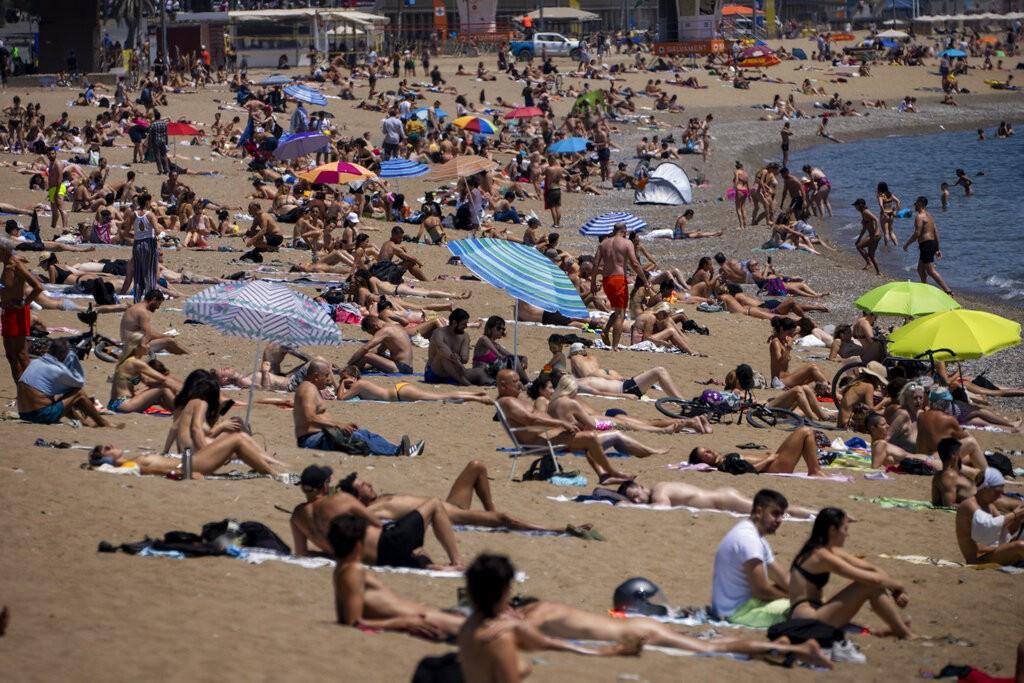 People sunbathe on the beach in Barcelona, Spain, Tuesday, June 8, 2021.