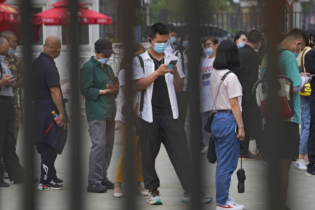 A manbrowses his smartphone lining up with masked residents to receive their vaccine at a vaccination point at the Central Business District in ...