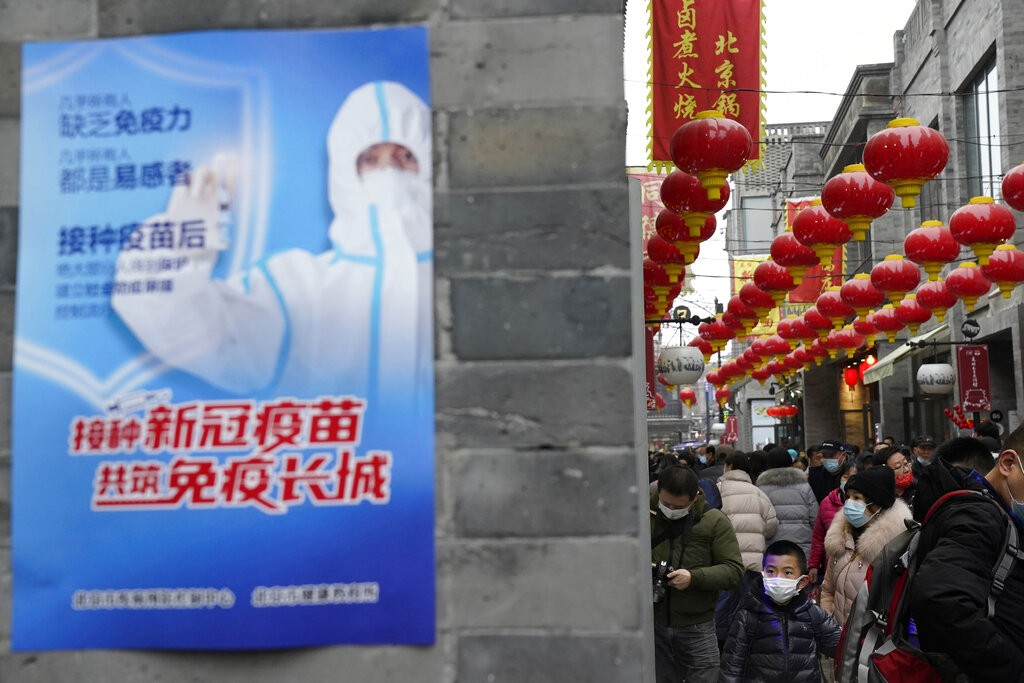"""A poster with the slogan """"Receive COVID-19 vaccination, jointly built an Immunity Great Wall"""" in Beijing on Feb. 14, 2021"""