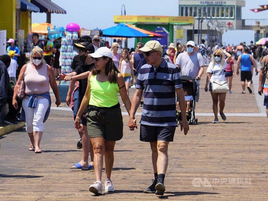 美國加州在6月15日宣布全面重啟,觀光景點聖塔蒙尼加碼頭,遊客脫下口罩,但仍有部分遊客習慣戴口罩。(圖/中央社)