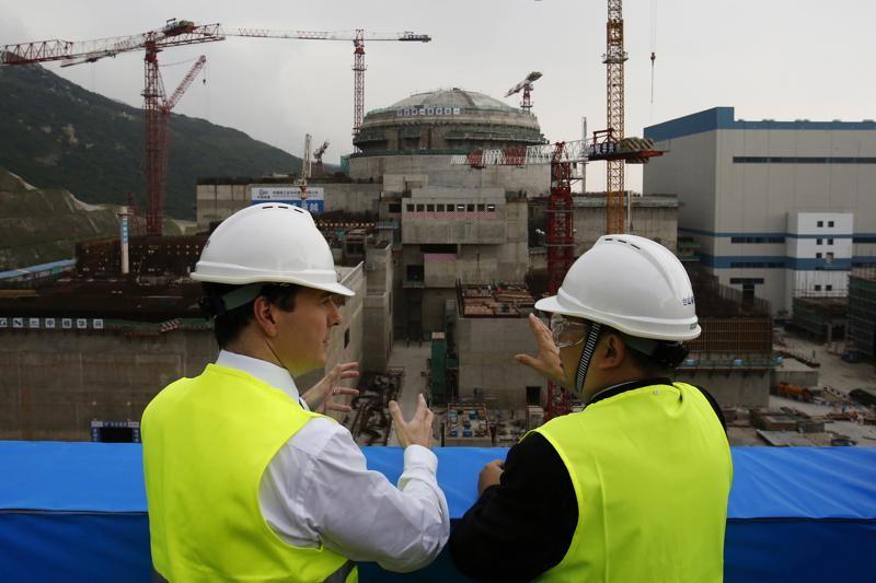 圖為2013年10月檔案照片,時任英國財政大臣喬治.奧斯本(左)與台山核電公司總經理郭黎明視察正在建設的核反應爐。(圖/美聯社).