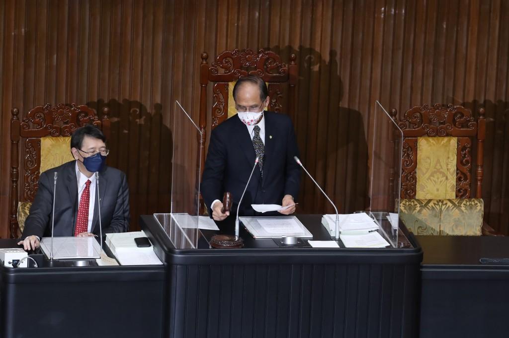 Legislative Speaker You Si-kun (center) marks the passage of a new COVID relief budget