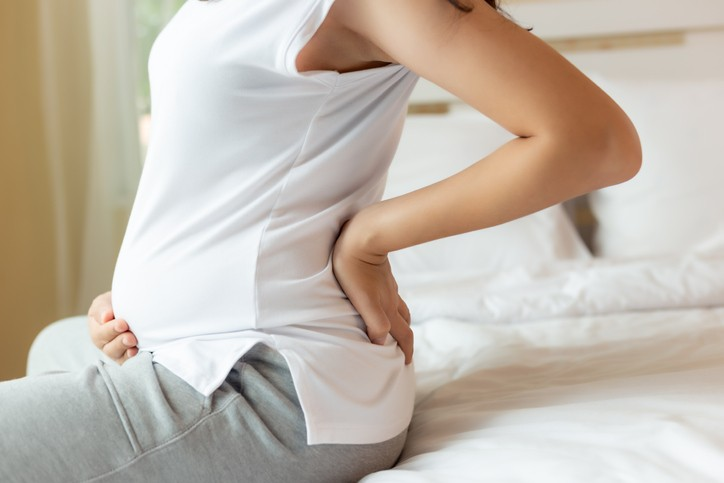 A pregnant woman sits on a bed. (Getty Images)