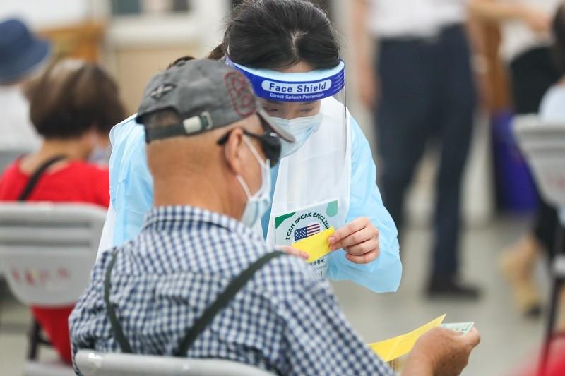 台北市政府24日開放75歲以上外籍人士施打AZ疫苗,由台北醫學大學附設醫院協助接種。北醫加派雙語工作人員在信義國中接種站協助民眾。 中央...