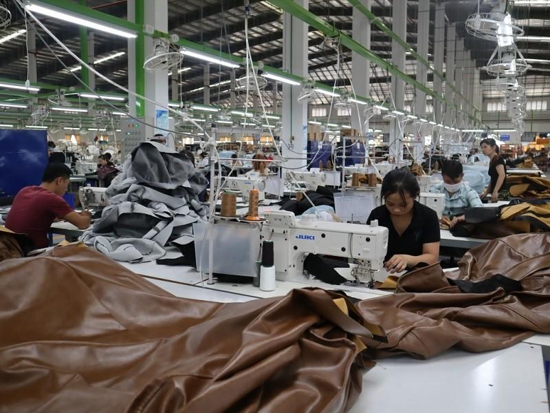 越南與台灣經貿往來活絡,有不少台商在越南投資,也有不少越南人在台灣工作。圖為在台資家具工廠車縫沙發皮的越籍工人。 中央社110年5月檔案照...