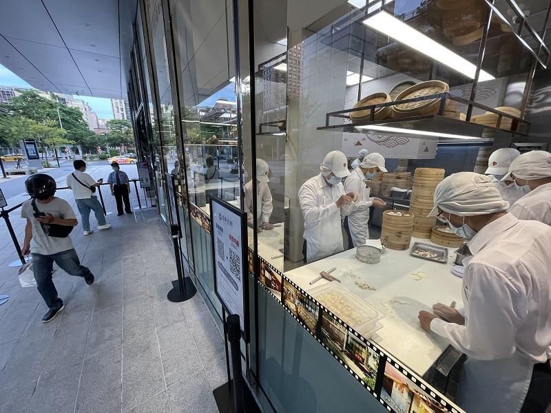 指揮中心8日公布有條件放寬餐飲內用,台北市政府9日宣布維持餐飲業、夜市等禁內用,只能外帶的原則。圖為一間連鎖餐廳廚師在廚房內準備料理, 門...