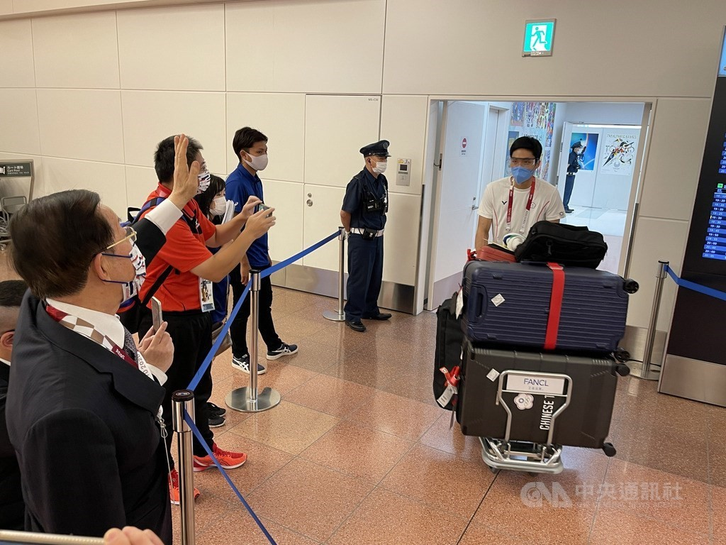 東京奧運台灣選手19日下午抵達羽田機場完成檢疫後,搭乘專車前往住宿地點。台灣羽球好手周天成(右)通關後準備迎接賽事。