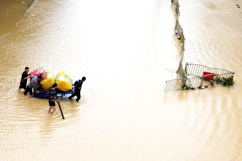 Residents move their belongings across a flooded street in Zhengzhou in central China's Henan province on Wednesday, July 21, 2021.