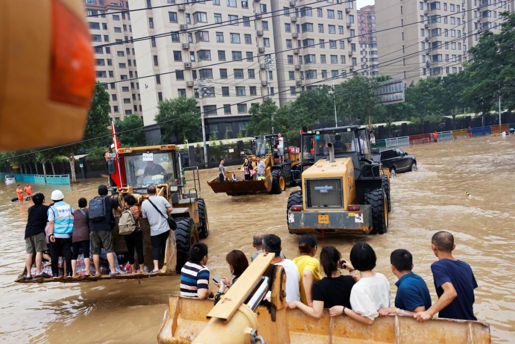 中國河南省鄭州市的民眾搭乘挖掘機具遷離受災區域。(圖/路透社)