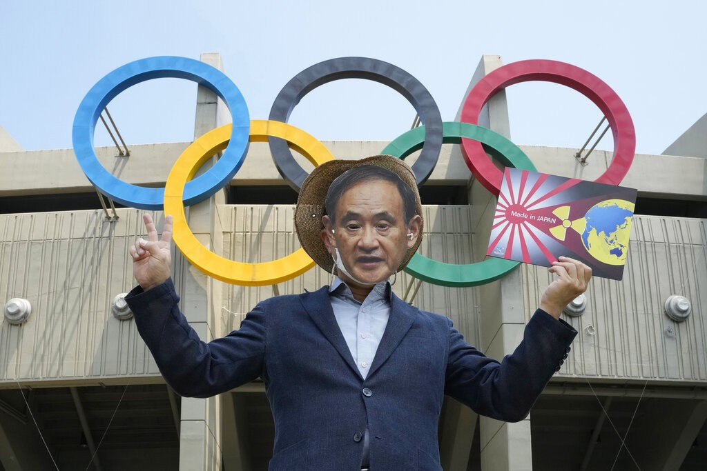 A South Korean environmentalist wearing a mask of Japanese Prime Minister Yoshihide Suga stages a protest against Tokyo 2020 Olympics due to safety co...