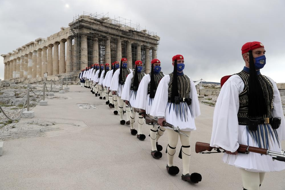 In this March 25, 2021 file photo, members of the Presidential Guard walk in front of the Parthenon temple atop of Acropolis Hill in Athens.