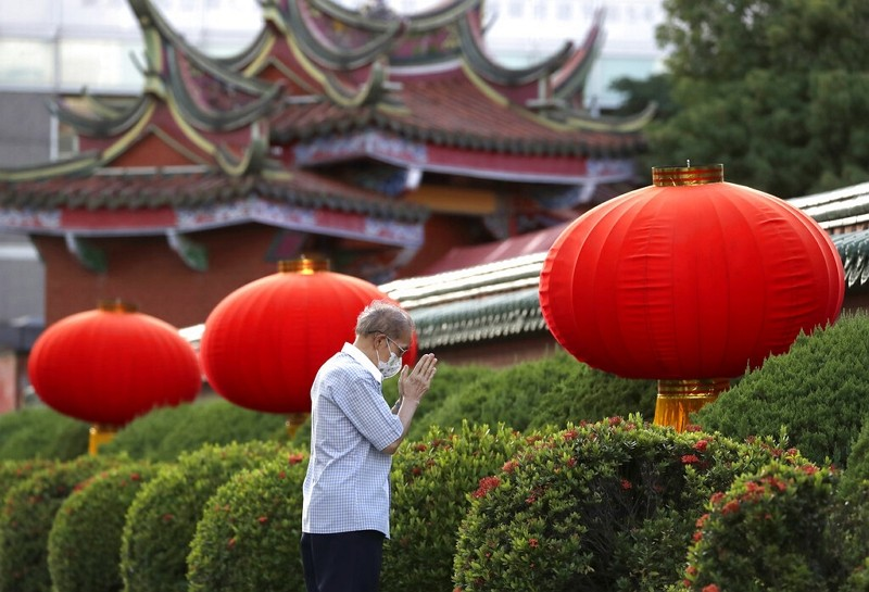 A man wearing a face mask to protect against the spread of COVID-19, prays outside Hsing Tian Kong Temple in Taipei,July 19, 2021.