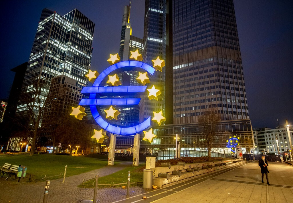 FILE - In this Thursday, March 11, 2021 file photo, a man walks past the Euro sculpture in Frankfurt, Germany.