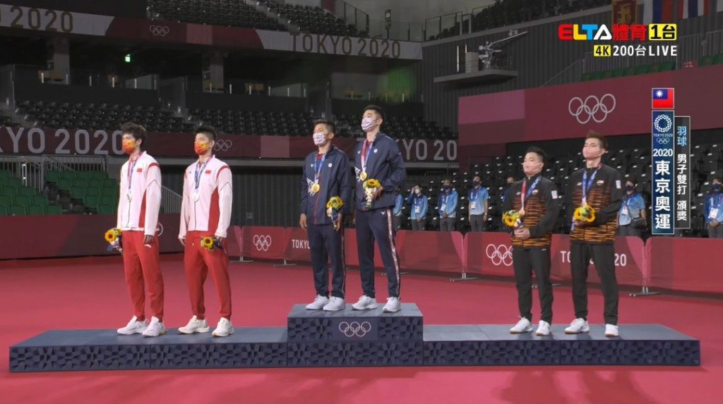 Taiwan national flag anthem plays as Lee and Wang stand on gold medal podium. (Facebook, ELTA Sports screenshot)