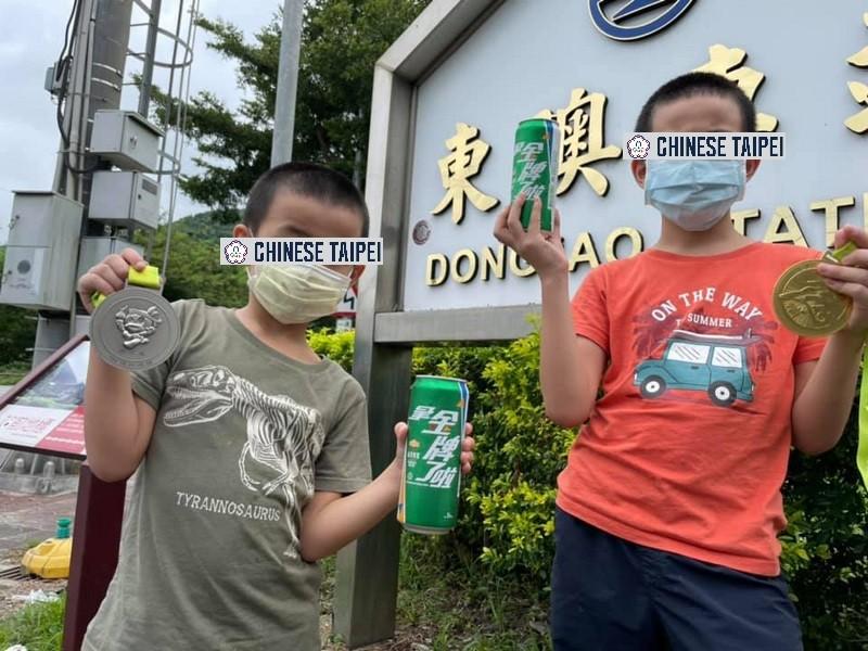 兩位小朋友在宜蘭東澳車站拍照, 搭上目前最夯的流行語「去東奧拿金牌」, 幫中華隊選手加油!(原圖: 中央社/TN 宇妍後製)
