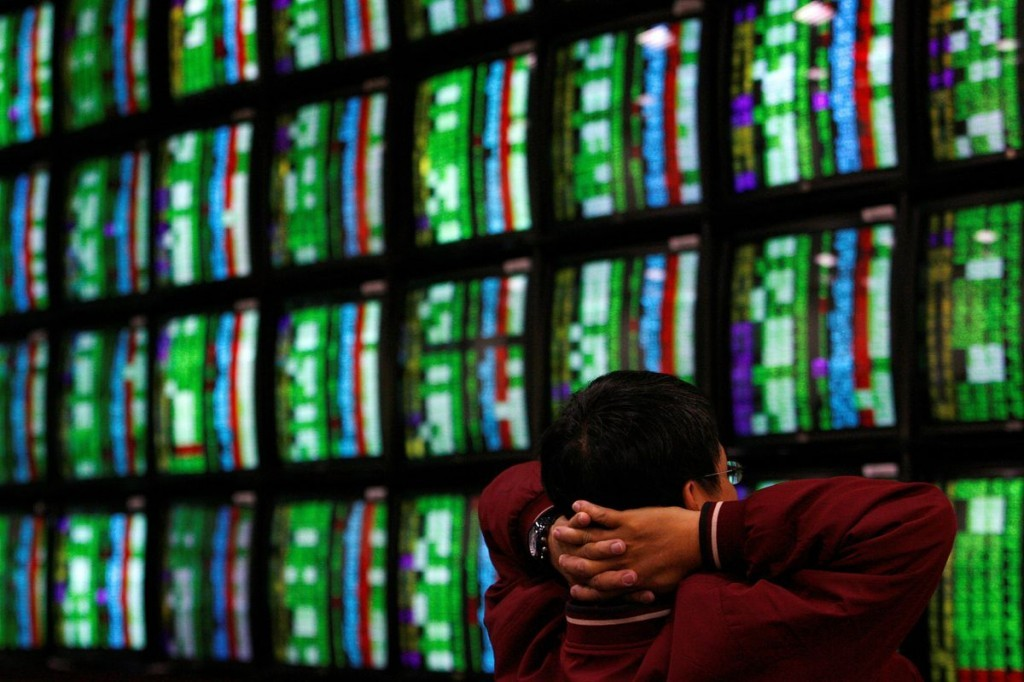 A man looks at stockmarket monitors inside a bank inTaipei. (Reuters photo)