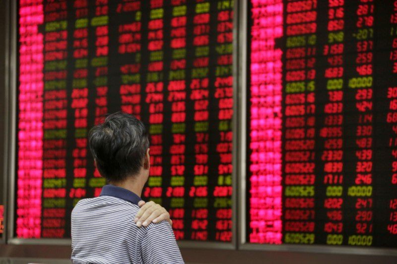 An investor looks at an electronic board showing stock information at a Beijing brokerage house. (Reuters photo)