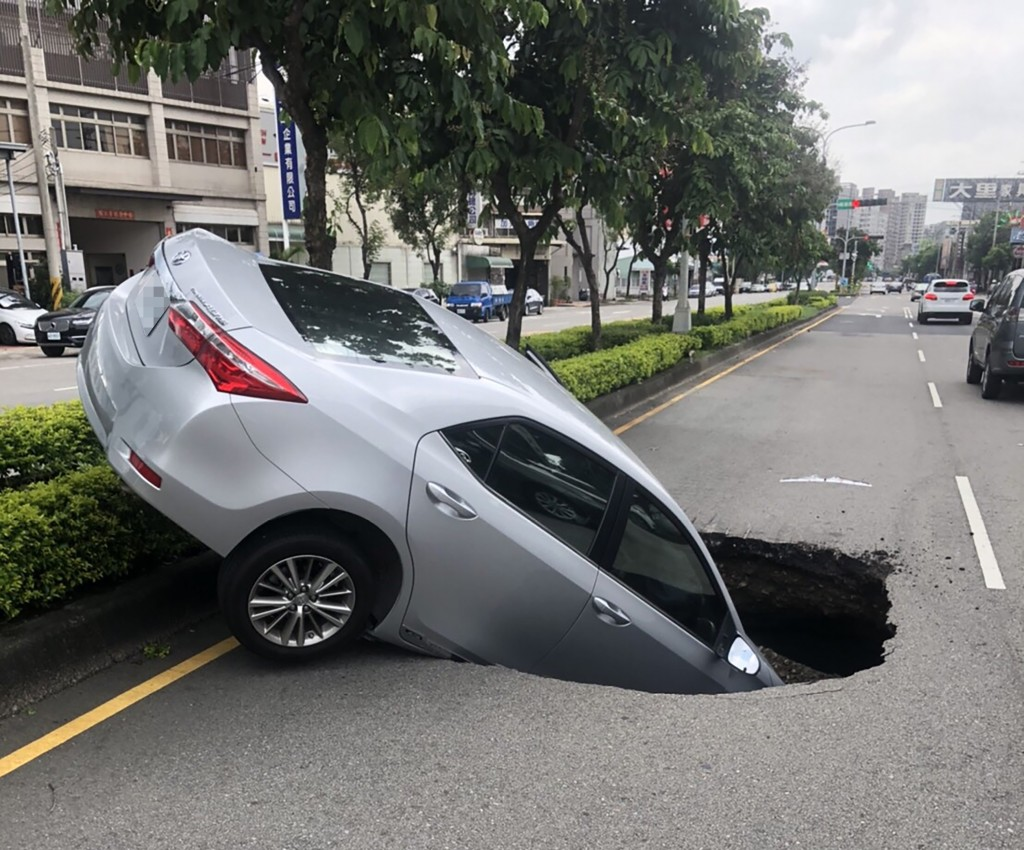 Taichung woman'scar swallowed by road in Taichung's Dali District. (Taichung Police photo).