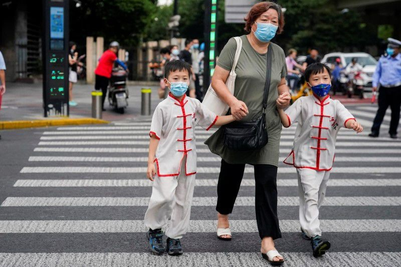 People wearing protective masks walk on a street, following new cases of the coronavirus disease (COVID-19), in Shanghai, China, August 10, 2021. (Reu...