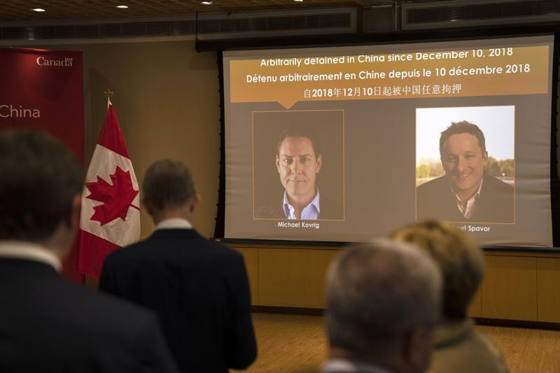 A video screen displays images of Canadians Michael Kovrig, left, and Michael Spavor at an event held in connection with the announcement of the sente...