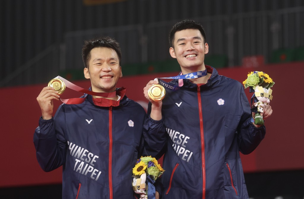 Taiwanese badminton players Lee Yang and Wang Chi-lin with their gold medals at the Tokyo Olympics.
