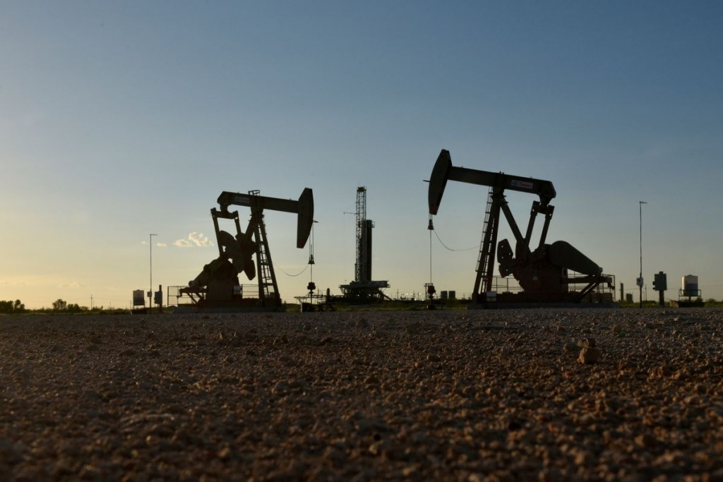 Pump jacks operate in front of a drilling rig in an oil field in Midland, Texas U.S. August 22, 2018. REUTERS/Nick Oxford