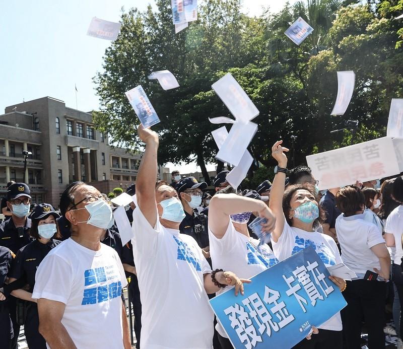 國民黨16日上午在行政院前舉行「紓困發現金」記者會就,黨籍立委舉看板、呼口號並在現場揮灑玩具紙鈔,要求政府發放現金紓困。中央社