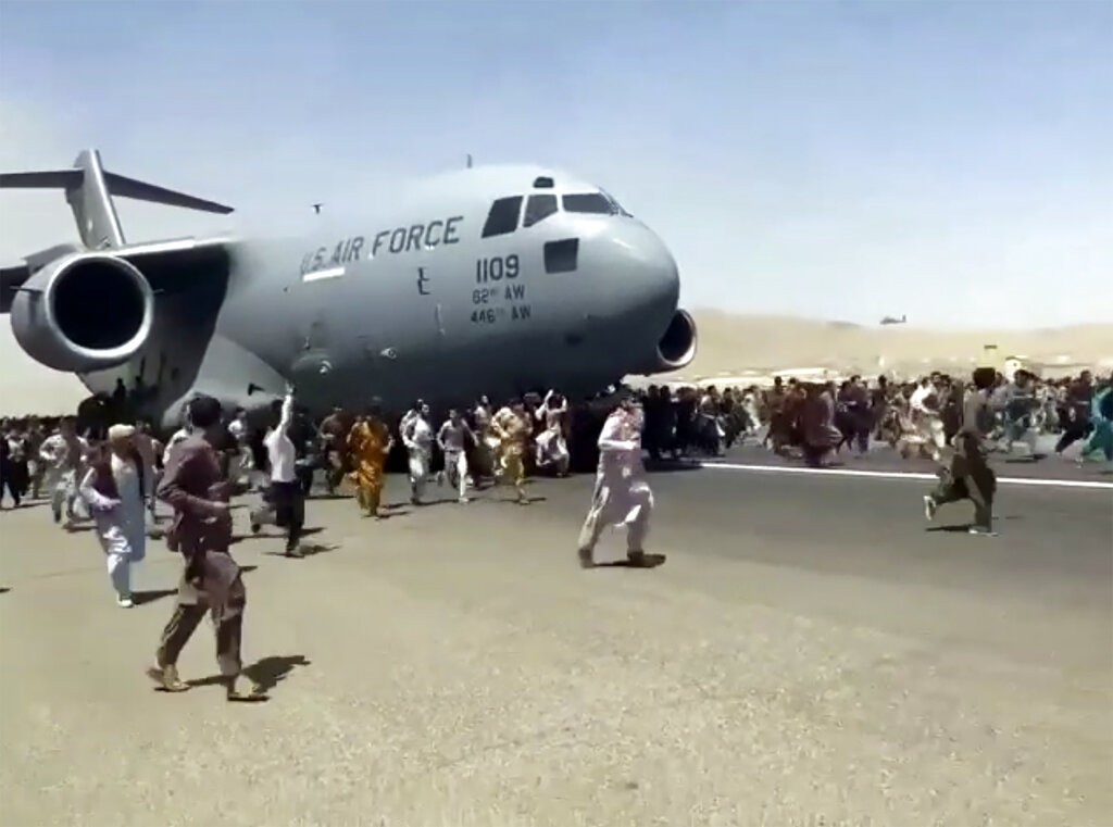 Hundreds of people run alongsideUSAFC-17 transport plane as it moves down runway of Kabul airport on Aug. 16.