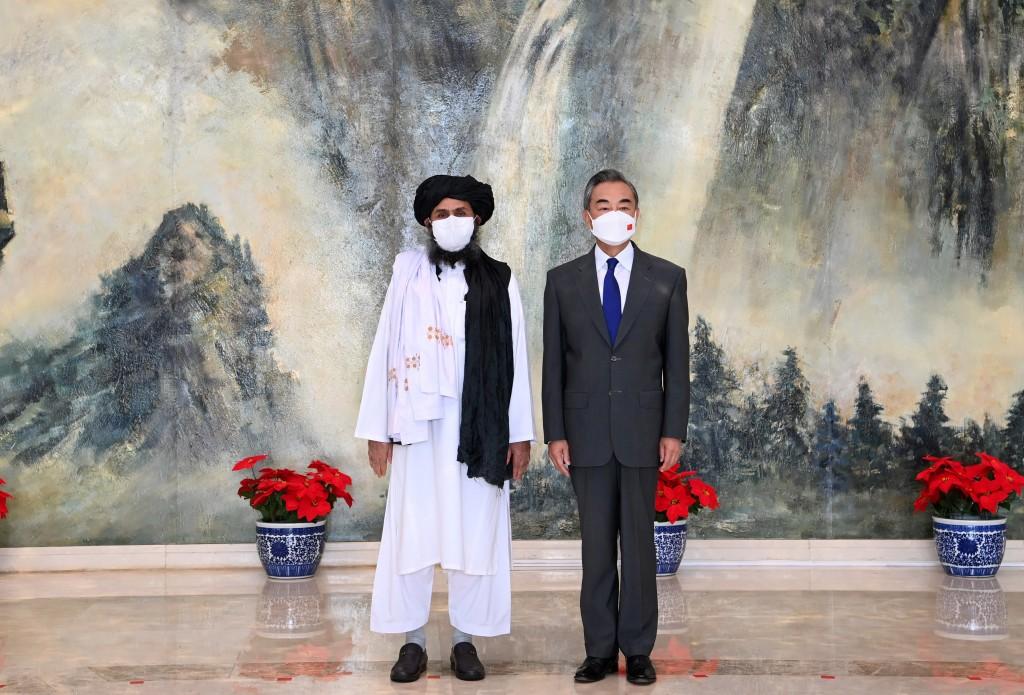 中國外交部在7月會見阿富汗塔利班代表團。圖為中國外交部長王毅(右)與塔利班政治委員會負責人巴拉達爾(左)。(圖/路透社)