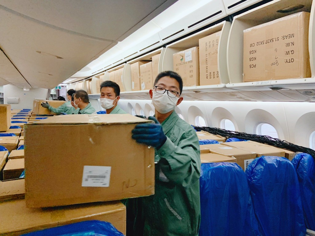 Crew loads boxes on passenger plane converted for cargo service. (Facebook, Xiamen Airlines photo)