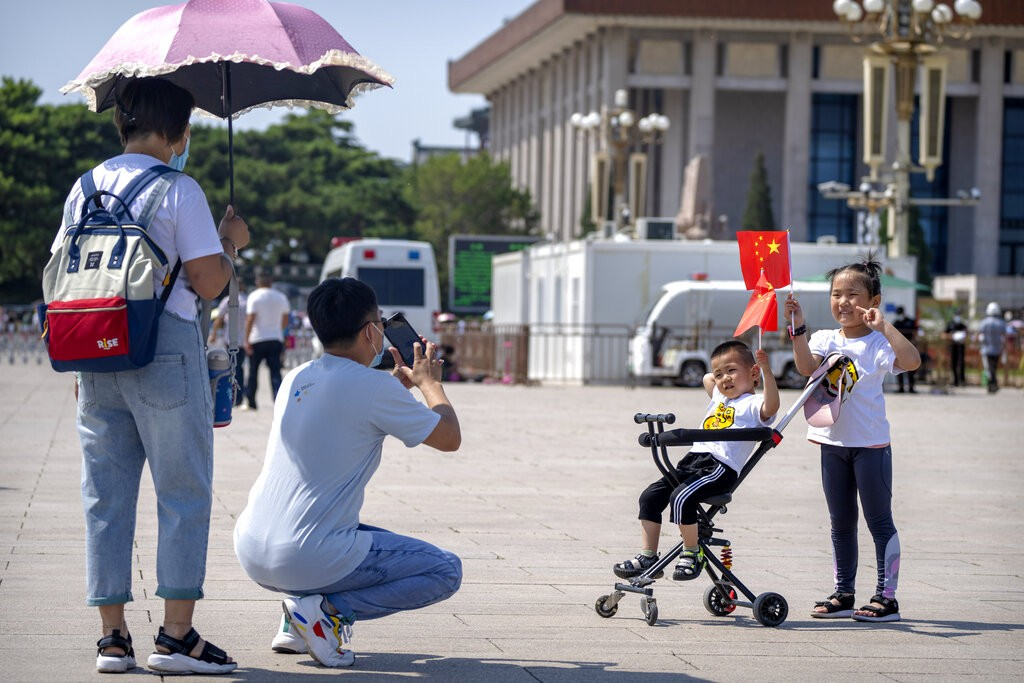 中國北京天安門廣場前一對父母為小孩拍照(美聯社圖片)。