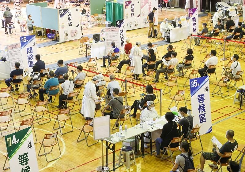 國產高端疫苗23日開放施打,許多民眾上午就依約定時間前來台大醫學院體育館接種疫苗。中央社