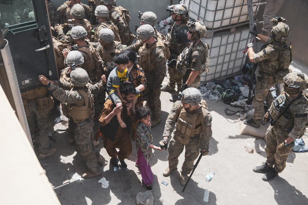 U.S. Marines and Norweigian coalition forces assist with security at an Evacuation Control at Hamid Karzai International Airport in Kabul, Afghanistan...