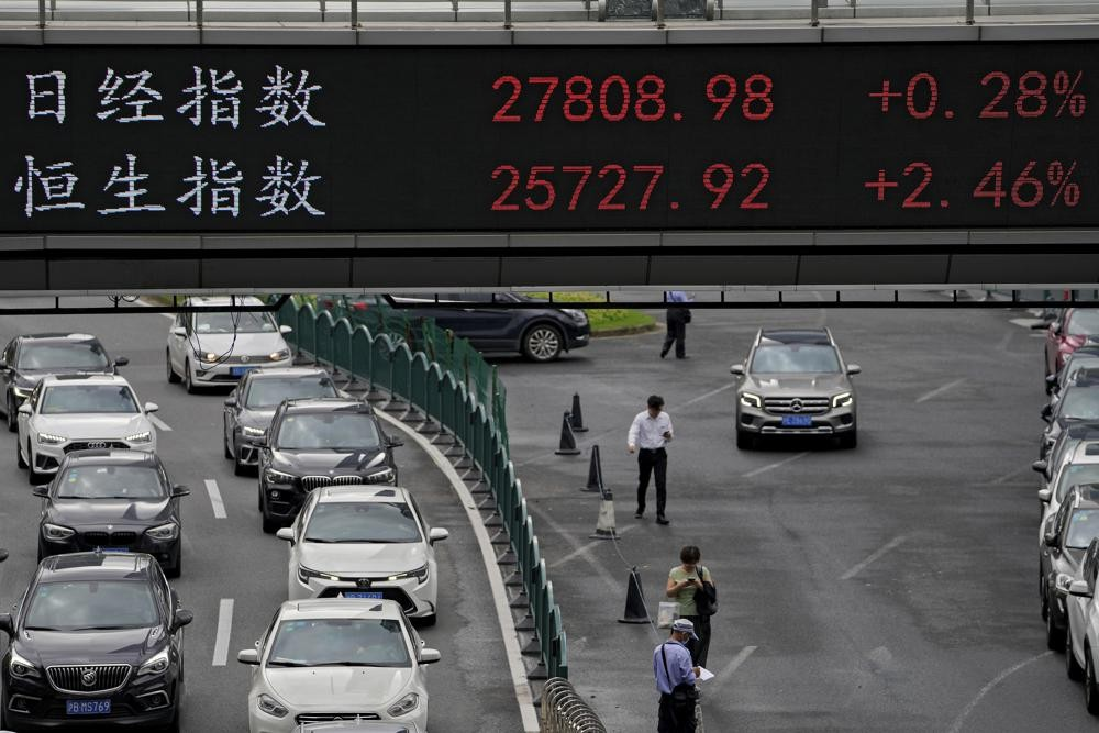 Motorists and people walk underneath an electronic board showing Hang Seng, bottom, and Nikkei Indexes at the Pudong Financial District in Shanghai, W...