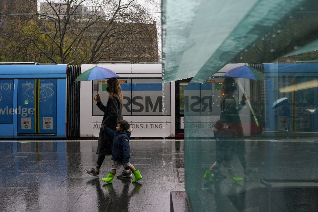 A masked woman with an umbrella walks with a child through the quiet city centre during a lockdown to curb the spread of a coronavirus disease (COVID-...