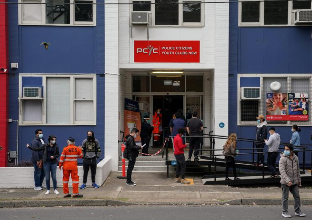 People wait in line outside a coronavirus disease vaccination clinic in Sydney.(Reuters photo)