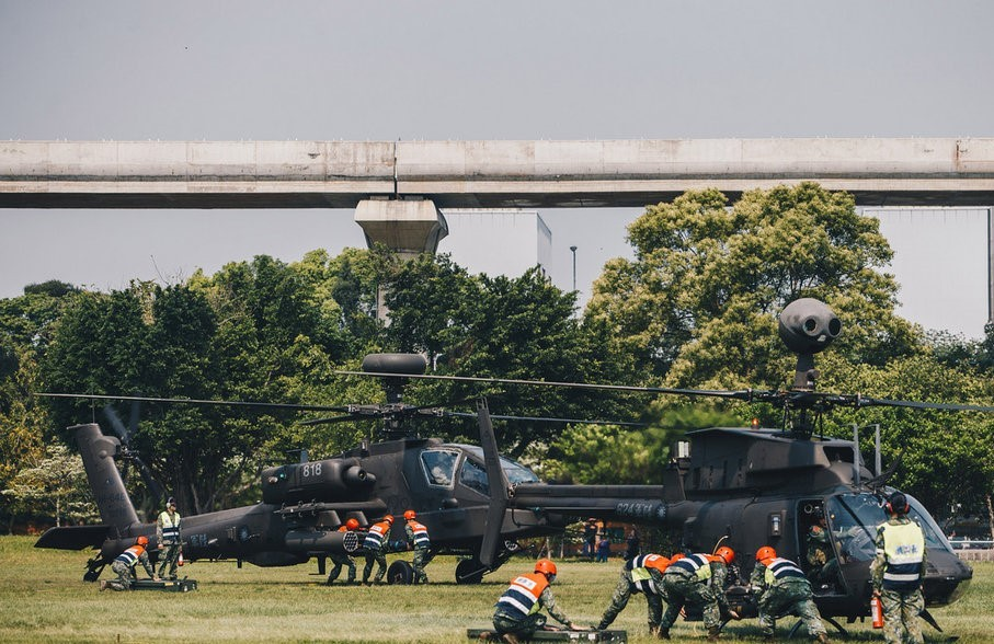Army personnel preparing Apache and Kiowa helicopters for flight.